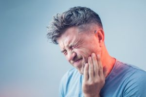 man holding mouth in pain who needs emergency dentist