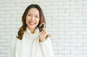 woman holding Invisalign clear aligner