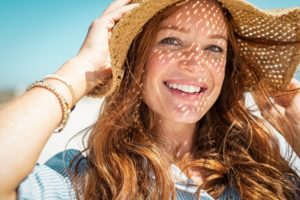 smiling woman wearing a beach hat