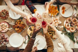 family clinking glasses during holiday dinner