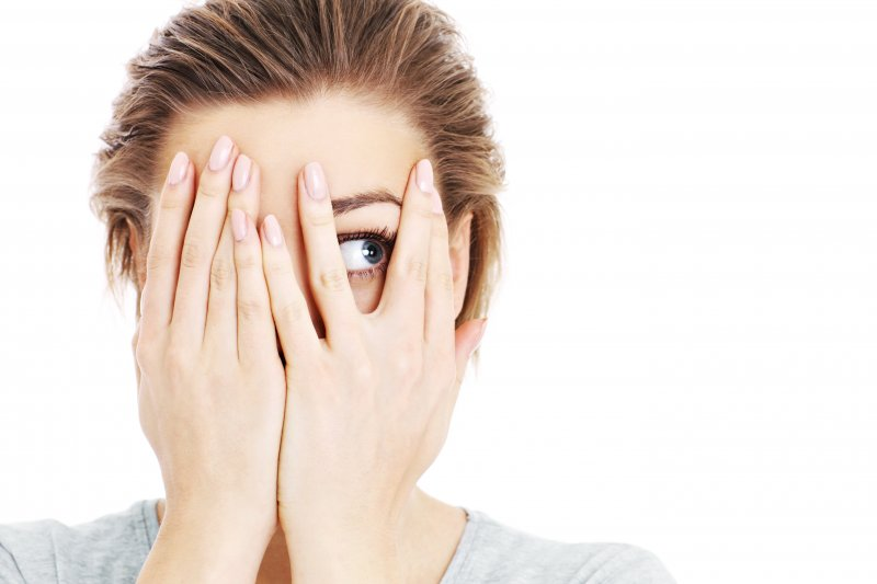 young woman covering her face out of fear