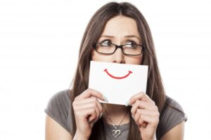 a woman hiding her smile behind a white card with a red smile drawn on it